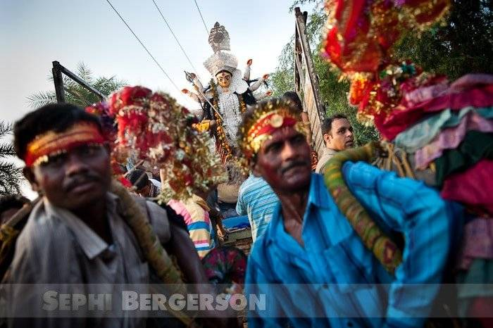An idol of the HIndu goddess Durga being transported on the back of a truck to the site of immersion during the Durga Puja festival, some forty km from Delhi