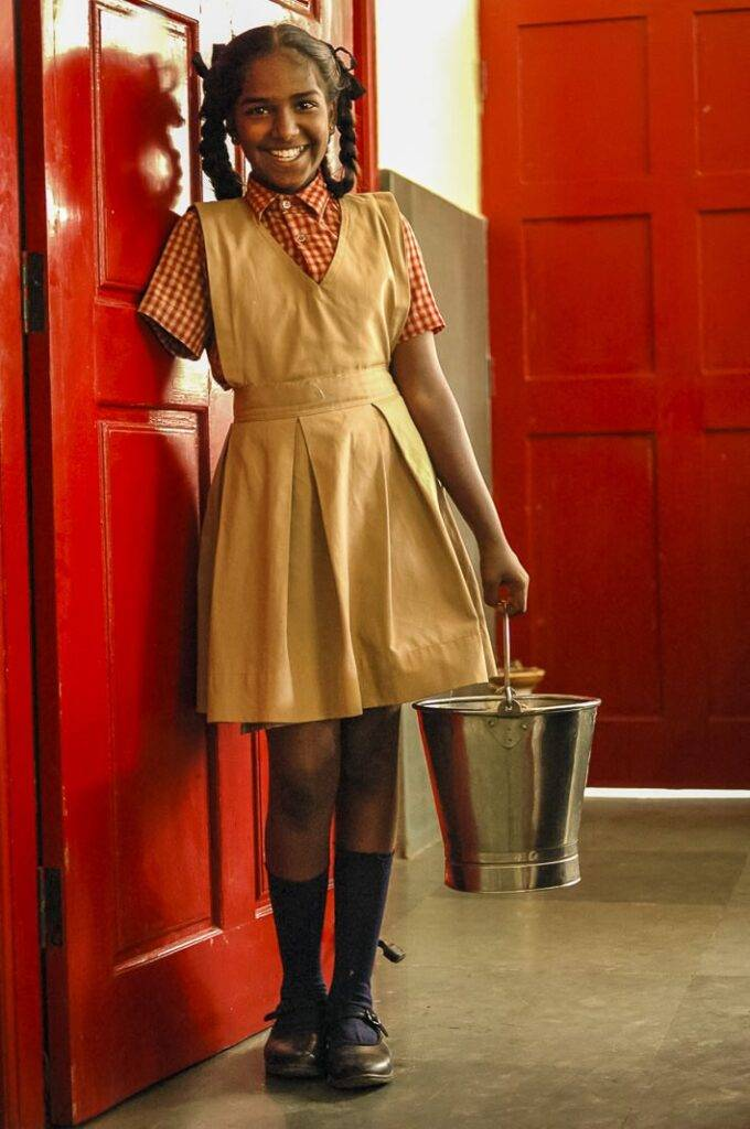 Rani (13) holding a bucket in the kitchen of APD School. The children take turns and today is her turn to help serve lunch. She lost her hand at the age of seven when she accidentally put it into her father's cement mixing machine.